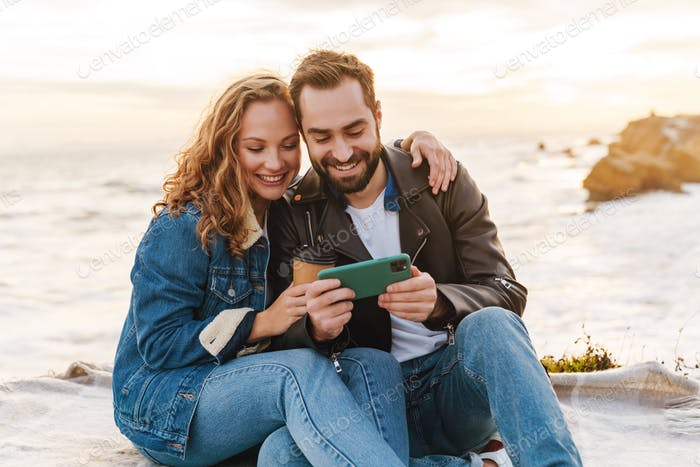 Image of young caucasian couple using cellphone while walking by seaside