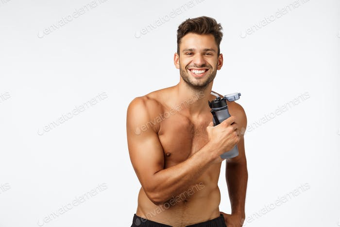 Muscular sexy and carefree, happy smiling sportsman standing shirtless, holding water bottle and