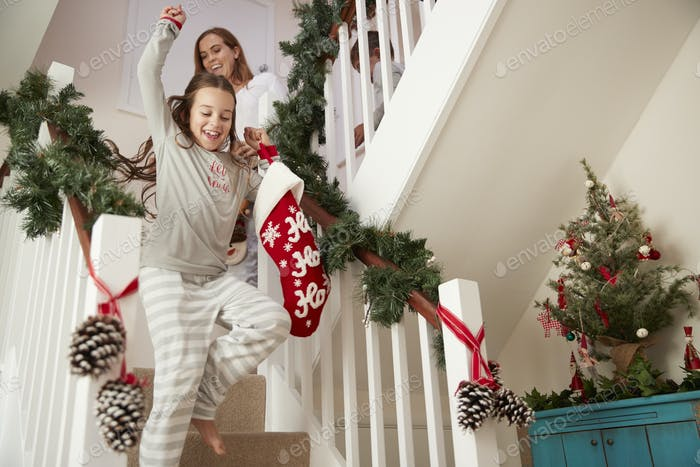 Excited Family Wearing Pajamas Running Down Stairs Holding Stockings On Christmas Morning