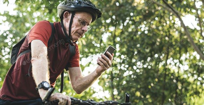Senior cyclist using the gps on his phone