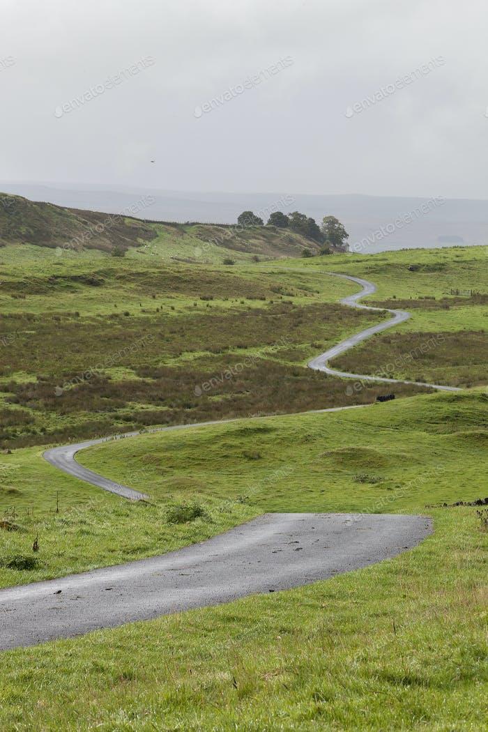 A winding road across open moorland countryside.