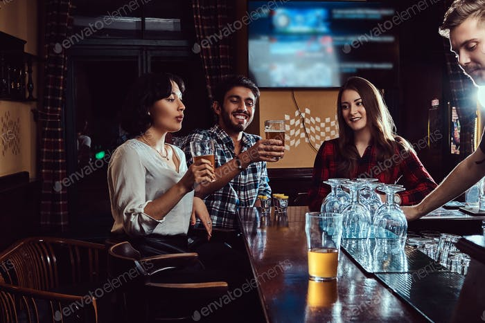 Group of happy multiracial friends resting and talking at bar or pub.