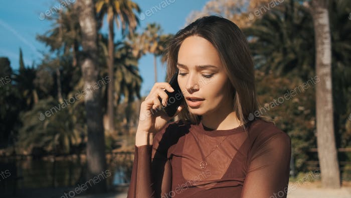 Beautiful sensual girl thoughtfully talking on smartphone with boyfriend in park