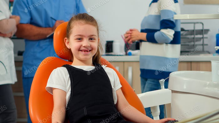 Portrait of little girl patient looking at camera waiting for pediatric stomatologist