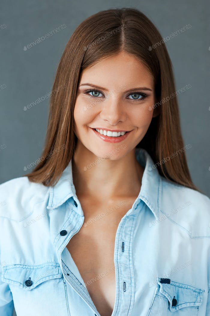 Sincere smile. Smiling young woman in shirt looking at camera while standing against grey background