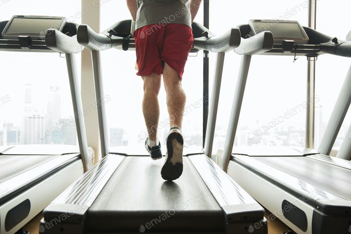 man exercising on treadmill in gym