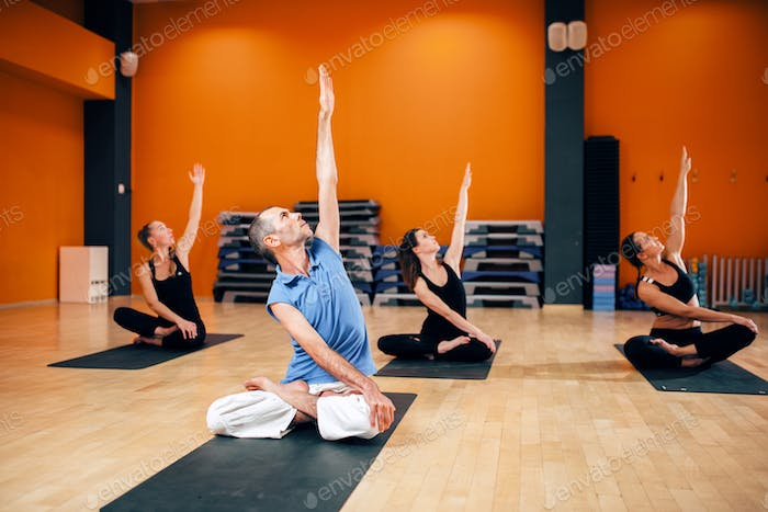 Group with trainer sitting in yoga pose