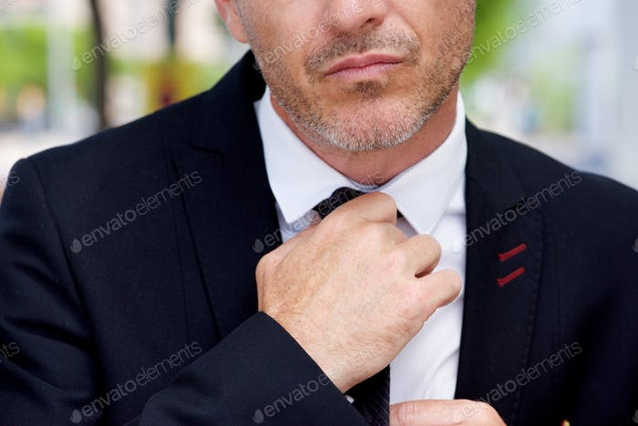 Close up serious businessman adjusting knot on tie