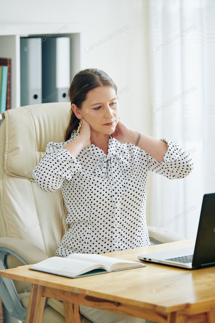 Businesswoman rubbing stiff neck
