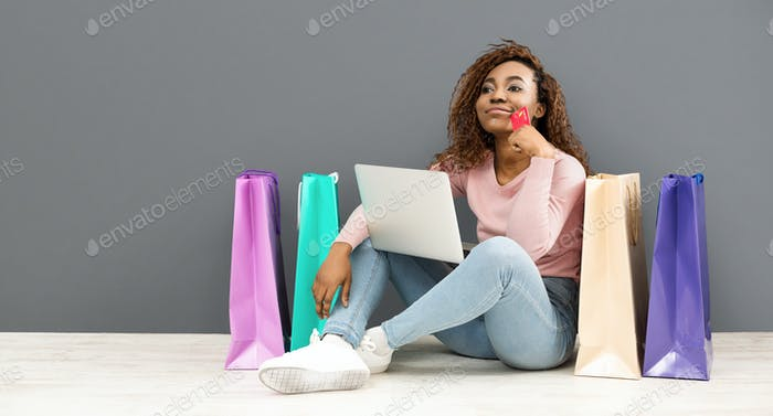 Dreamy girl with credit card making shopping using laptop