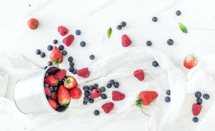 Metal bucket, strawberries, raspberries, blueberries and mint leaves, white wooden background