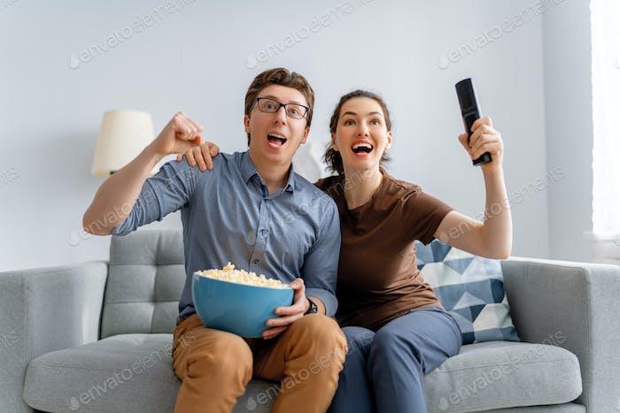couple with popcorn sitting on sofa