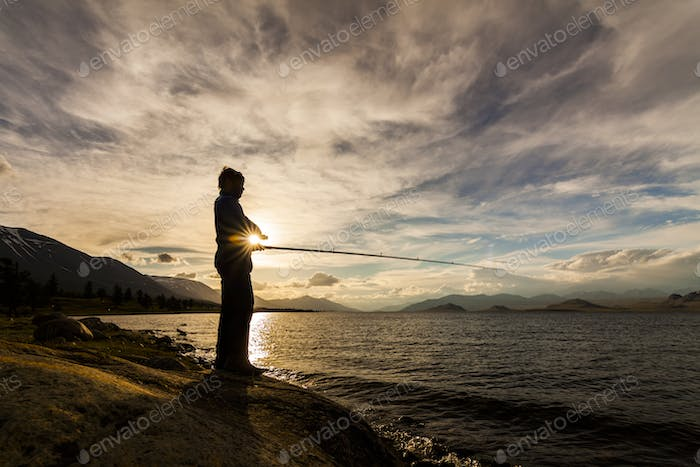 Silhouette of a fisherman with a fishing rod on the background of the river and mountains