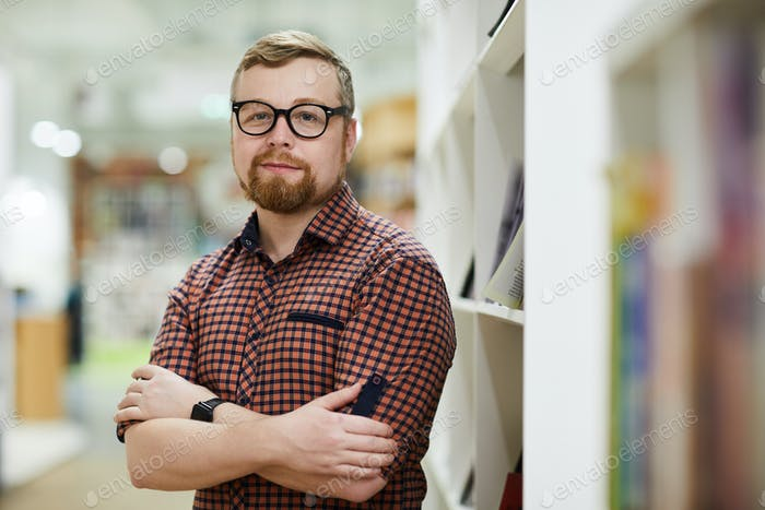 Confident bearded bookstore manager