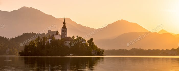 Insel im Bled See mit orangefarbenen Julischen Alpen sillhouette