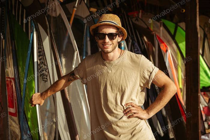 Man in hat and sunglasses standing at the surf shack