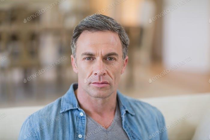 Portrait of man sitting in living room
