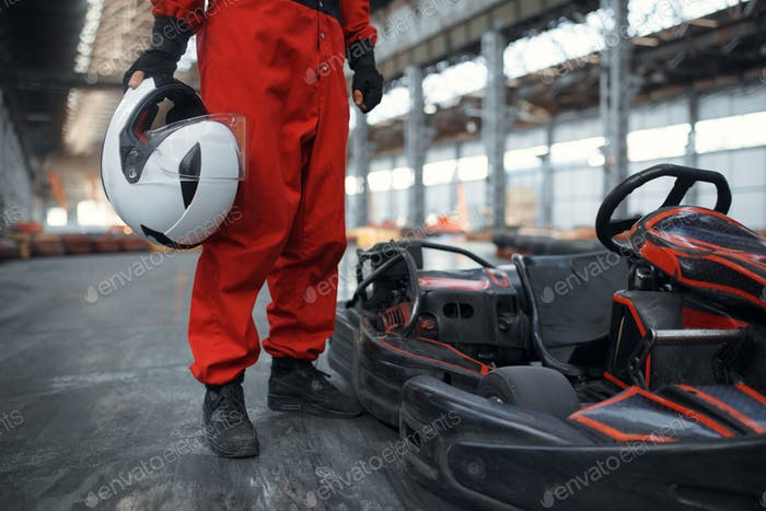 Racer mit Helm posiert in der Nähe von Go Kart Auto, Karting