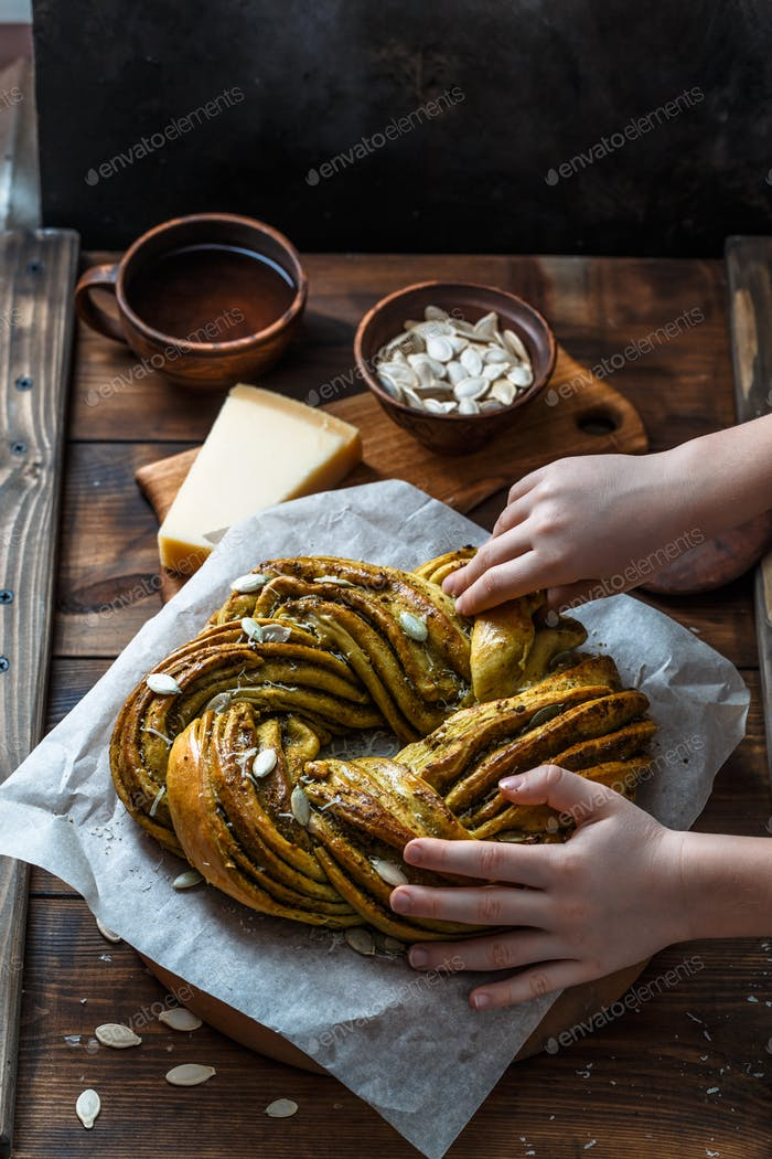 Babka Brioche Wreath with Pesto and Parmesan with hands