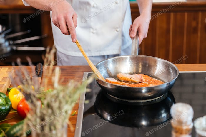 Hands of chef making fresh salmon steak on frying pan