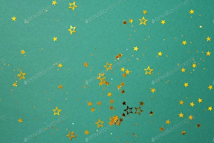 Golden star sparkles on green background