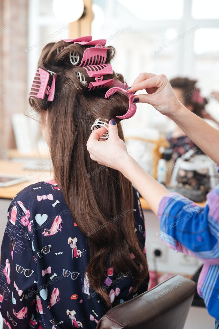 Hairdresser taking off curlers from woman long hair