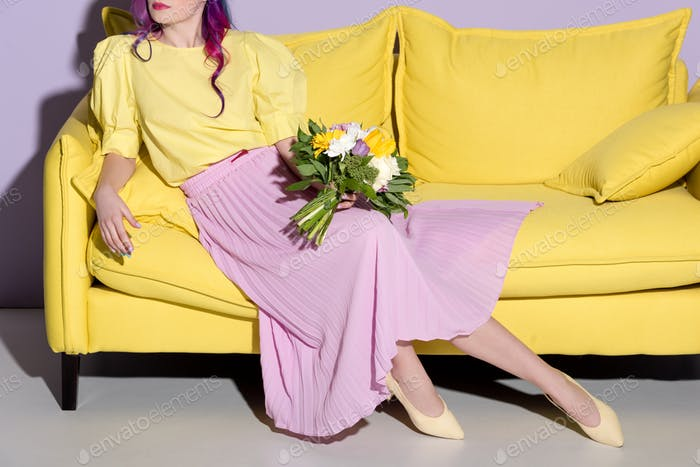cropped shot of woman sitting on yellow couch with floral bouquet
