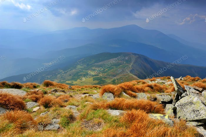 Fantastic mountain landscape. Autumn, dramatic sky with clouds.