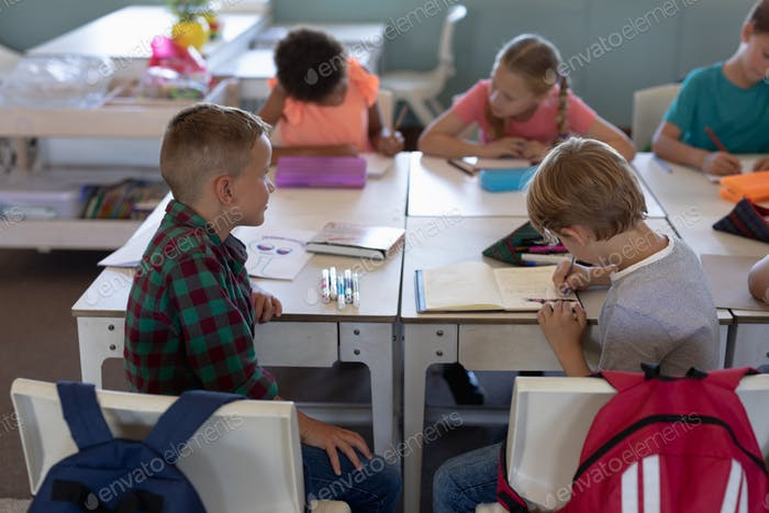 Schuljungen sitzen an Schreibtischen in einer Grundschule Klassenzimmer