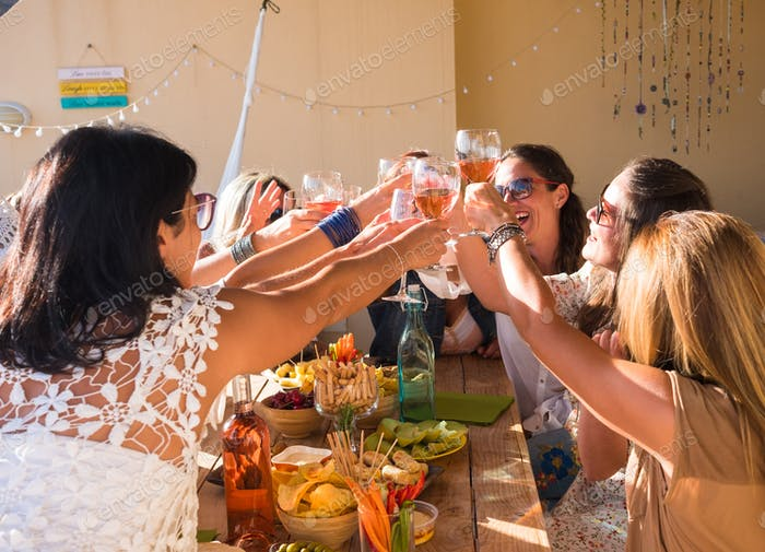 Große Gruppe von Freundinnen, die eine Party auf der Terrasse genießen und mit Rotwein anstoßen.