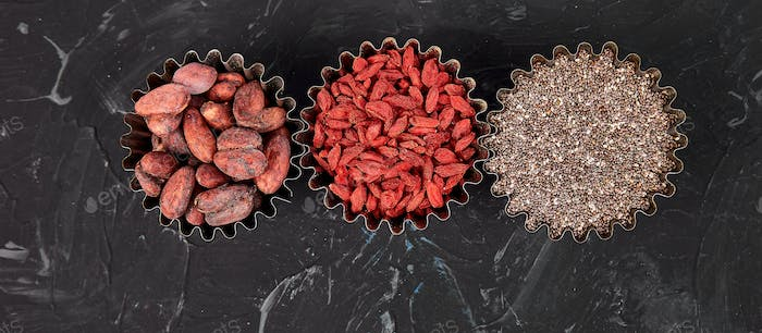 Banner of Various superfoods in small bowl on black background.