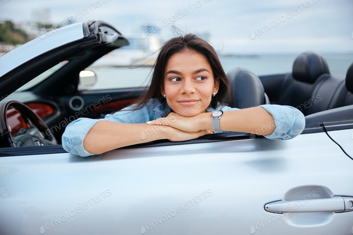 Smiling young woman sitting inside her convertible car