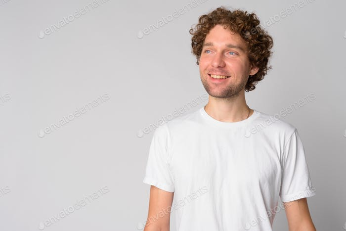 Portrait of happy man with curly hair thinking