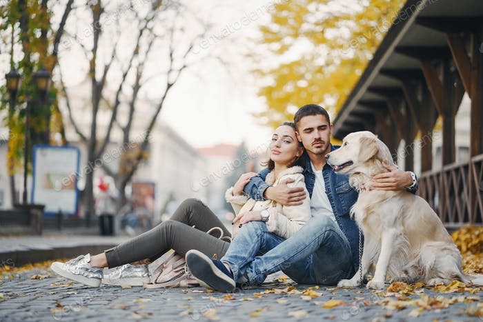 couple walking their dog on a sunny autumn day
