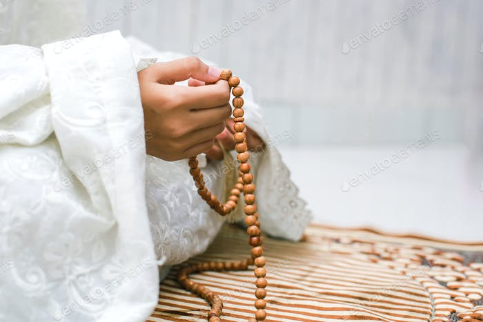 Mujer musulmana sosteniendo rosario