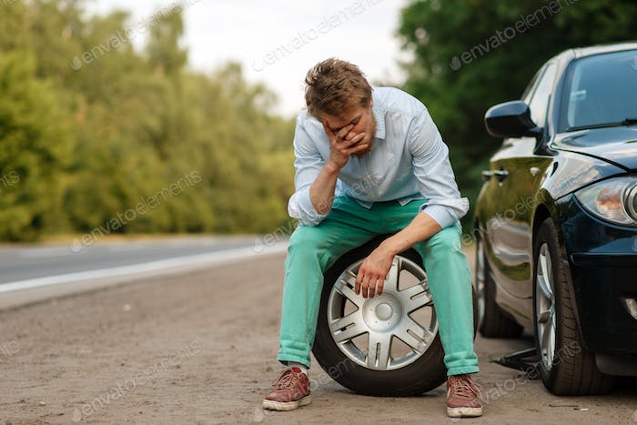 Car breakdown, tired man sitting on spare tyre