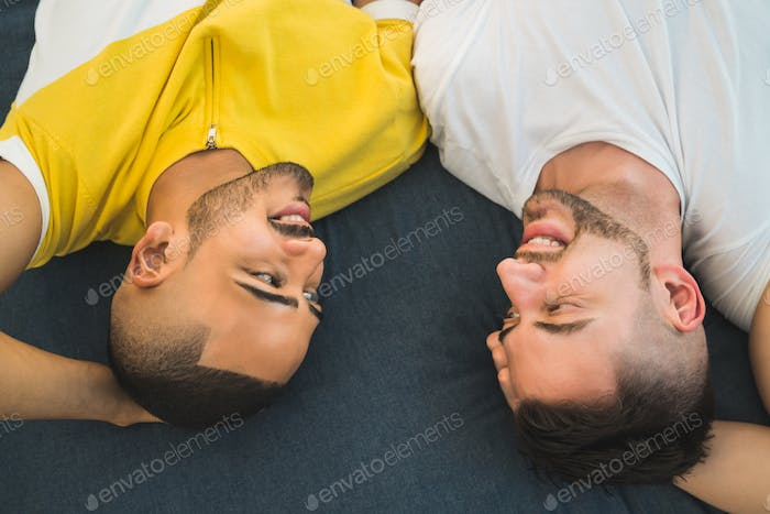 Gay couple laying down on the floor.