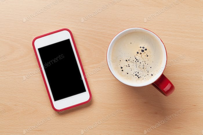 Coffee cup and smartphone on wooden desk
