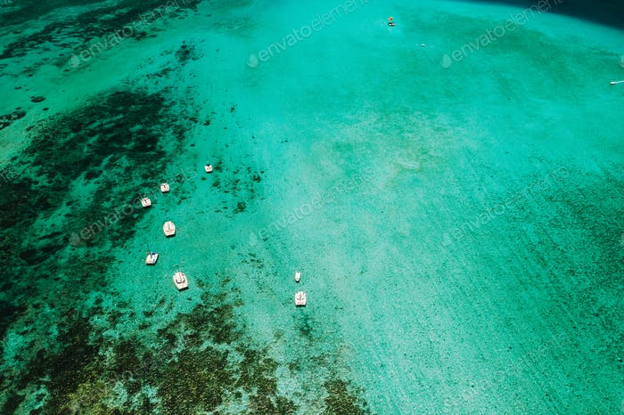 Aerial picture of the east coast of Mauritius Island. Boat sailing in turquoise lagoon