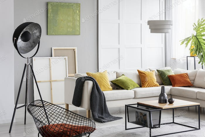 Table next to corner sofa with cushions in bright flat interior