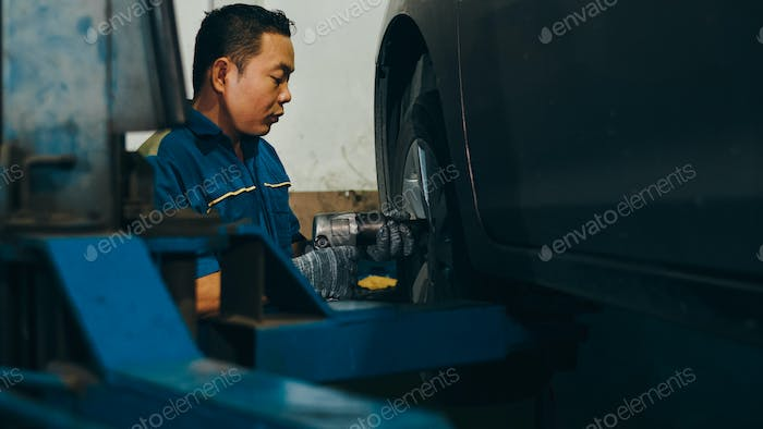 Car mechanic changing a car tire on lifted automobile at repair service station.