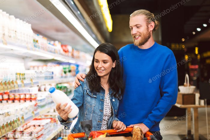 Young smiling couple with trolley full of products happily choos