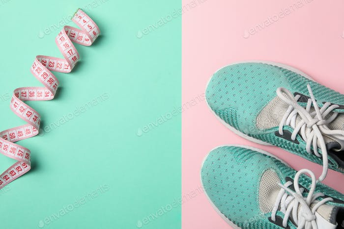 Measuring tape and sneakers on two tone background