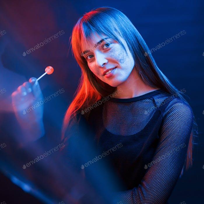Sweet candy. Studio shot in dark studio with neon light. Portrait of young girl