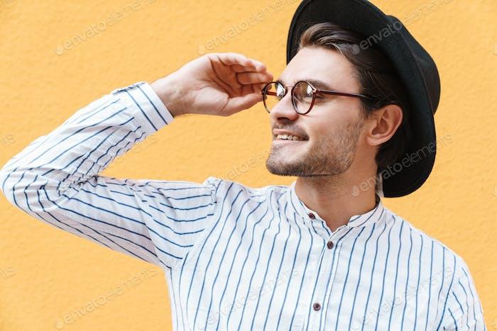 Bild von jungen glücklichen Mann trägt Brille und schwarzen Hut lächelnd und Blick beiseite auf copyspace