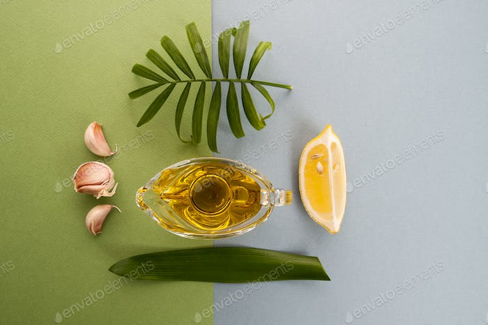 Fresh garlic, lemon and olive oil on a blue-green background.