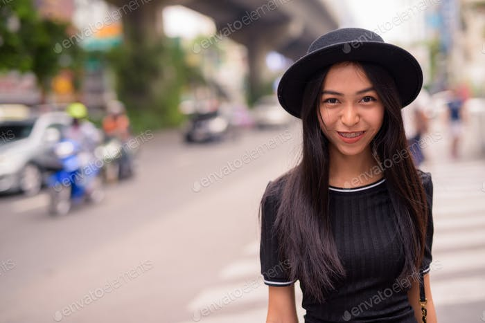 Happy young beautiful Asian tourist woman in the city streets