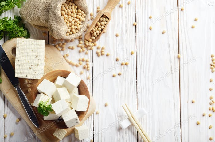 Sojabohnenquark Tofu in Holzschale und im Hanfsack auf weißem Holz