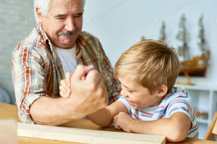Little Boy Armwrestling with Grandpa