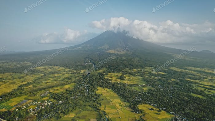 Mayon volcano erupts at Philippines countryside aerial. Tropic green forest plants and grasses